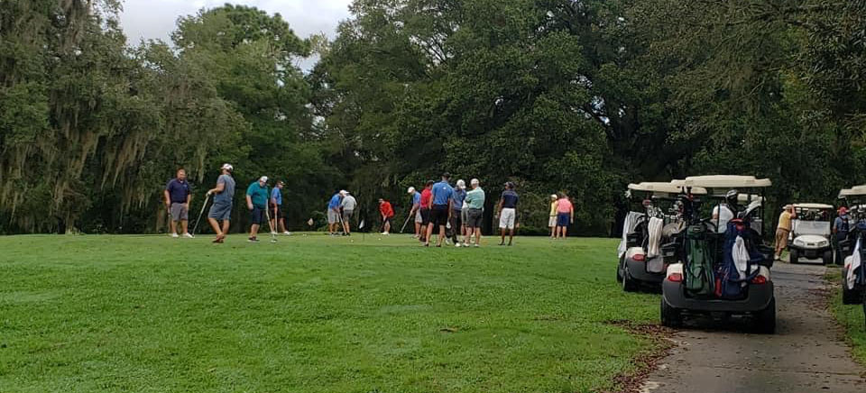 golfers gathering around the green